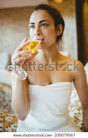 Woman enjoying her glass of champagne at the spa - stock photo