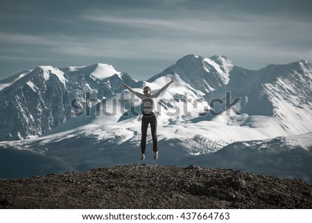 woman enjoying mountains. trying to fly. - stock photo