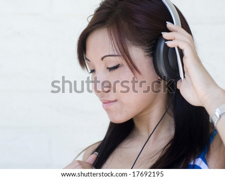 Woman enjoying music through headphones with eyes closed - stock photo