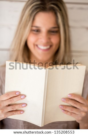 Woman enjoying reading a book at home - stock photo