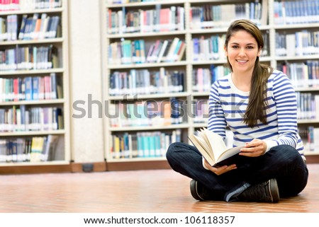 Woman enjoying reading and sitting at the library - stock photo
