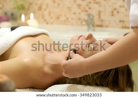 Woman enjoying stone therapy/A female receiving massage and hot rock treatment to back and neck at a beauty salon or day spa facility/ Female Receiving a Relaxing Massage Treatment - stock photo