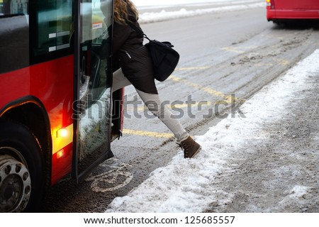 Woman entering bus in winter - stock photo