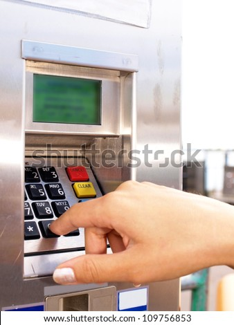 Woman entering PIN on a ticket vending machine - stock photo
