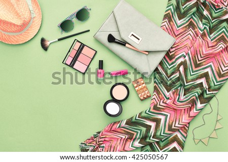 Woman essentials. Unusual overhead, top view. Fashion stylish clothes, cosmetics, makeup accessories set. Urban summer girl colorful outfit. Stylish handbag clutch, trendy pants, necklace sunglasses. - stock photo