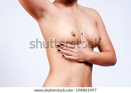 Woman examining her breast - stock photo