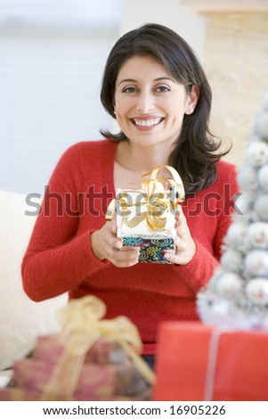 Woman Excited To Open Christmas Present - stock photo