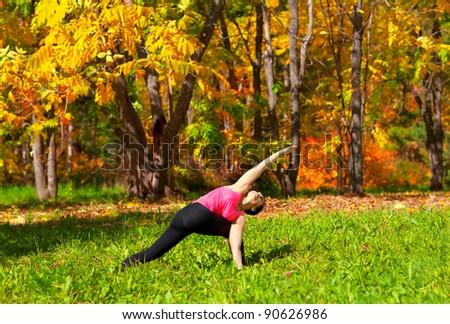 Woman exercises in the autumn forest yoga parivrita parshvakonasana pose - stock photo