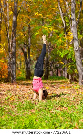 Woman exercises in the autumn forest yoga pinch mayurasana pose - stock photo