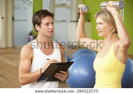 Woman Exercising Being Encouraged By Personal Trainer In Gym - stock photo
