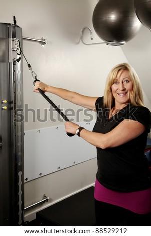 Woman exercising on a machine - stock photo