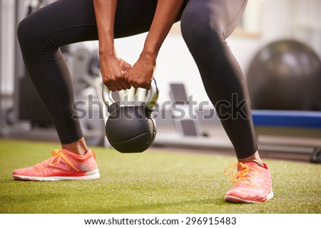 Woman exercising with a kettlebell weight, low-section crop - stock photo