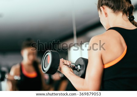 Woman exercising with dumbbell in fitness center, looking at mirror - stock photo