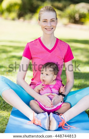 Woman exercising with her baby in park - stock photo