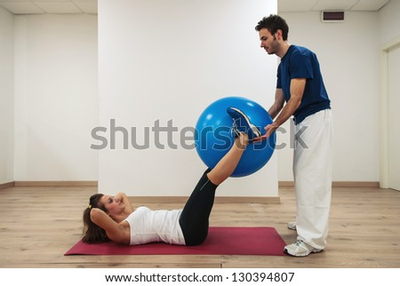 Woman exercising with her personal trainer at the gym. - stock photo