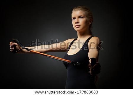 Woman exercising with resistance band on dark - stock photo