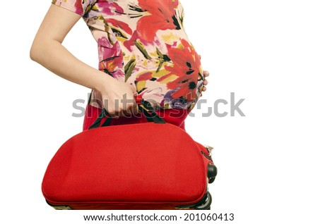 Woman expecting a baby holding a suitcase in her hands. Close up on pregnant belly isolated on white. Pregnant woman travelling. - stock photo