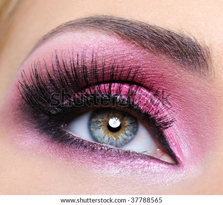 Woman eye with bright crimson make-up and long eyelashes - stock photo