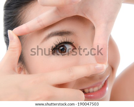 Woman face and eye care and she making frame with hands - stock photo