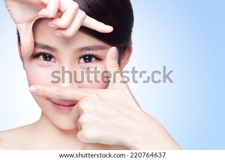 Woman face and eye care and she making frame with hands, asian beauty - stock photo