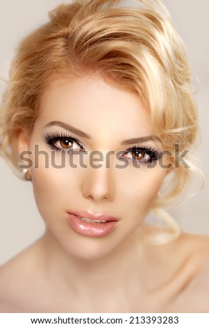 Woman face close up. A pretty young blond trendy. Girl with a beauty face. Beautiful female face with luxury make-up - stock photo