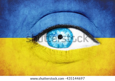 Woman face painted with flag of Ukraine - stock photo