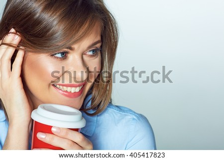 Woman face portrait. Smiling girl posing on white background with red coffee cup. - stock photo
