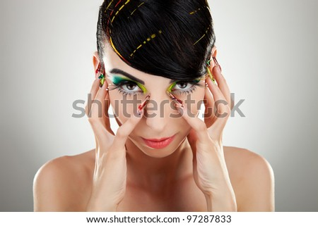 Woman face with color makeup and manicure on studio background - stock photo