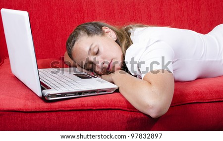 Woman falls asleep after a hard work afternoon. She sleeps over her laptop - stock photo