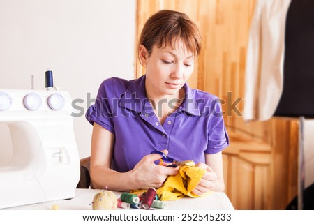 Woman fashion designer sewing with sewing machine - stock photo