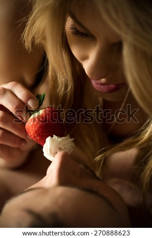 Woman feeding her lover with strawberry and cream - stock photo