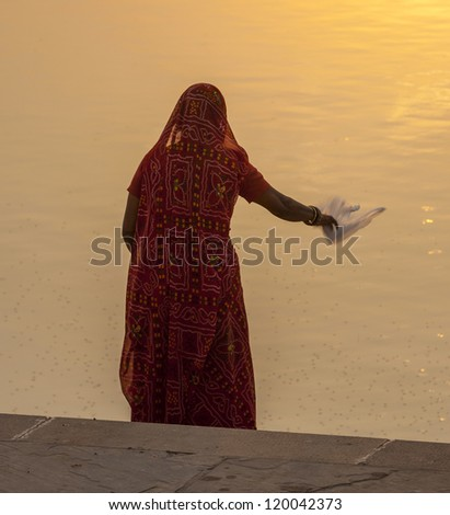 woman feeds the fishes in the holy lake in Pushkar - stock photo