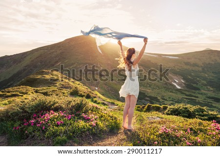Woman feel freedom and enjoying the nature in the mountains with blue tissue in hands on sunset - stock photo