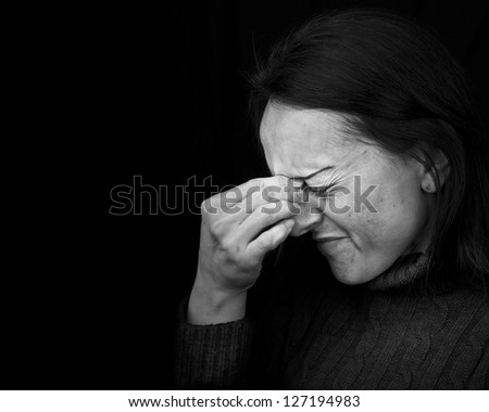 woman feeling pain, frowning with hand on head with black background and copy space - stock photo