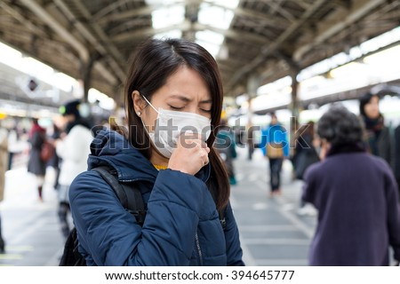 Woman feeling sick and wearing face mask in metro station platform - stock photo