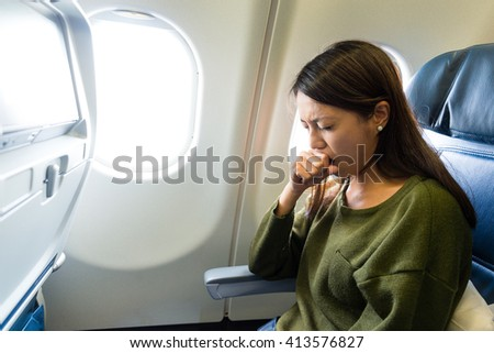 Woman feeling sick inside air plane - stock photo