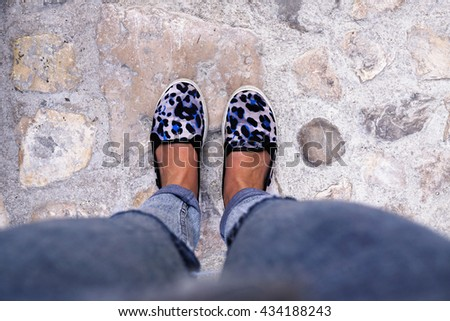 Woman feet and legs with blue leopard print shoes, on the sidewalk. - stock photo