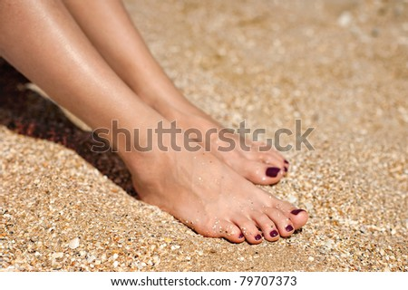 Woman feet with dark pedicure relaxing on the sand - stock photo