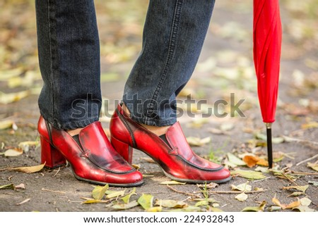 Woman feet with red fashion shoes on a late autumn shooting - stock photo