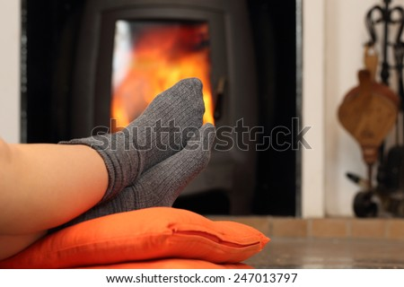 Woman feet with socks resting near fire place with a warmth background - stock photo