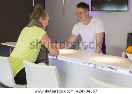 Woman filling in a registration form with help from man at a desk in health club - stock photo