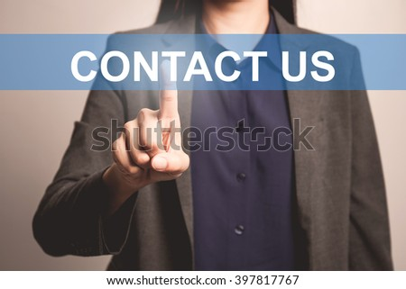 woman finger pointing at the camera with contact us word - stock photo