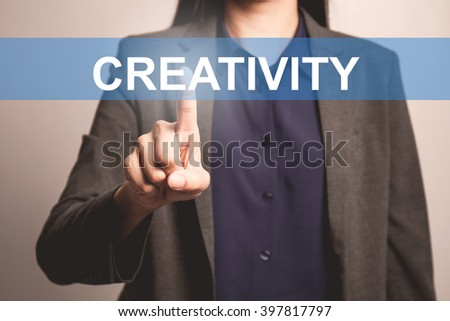 woman finger pointing at the camera with creativity word - stock photo