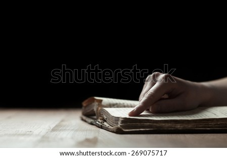woman finger presses on old bible book in a dark - stock photo