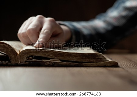 woman finger presses on old bible book over wooden table and reading - stock photo