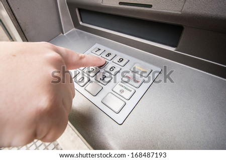 woman finger pressing password number on ATM machine - stock photo