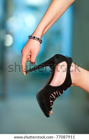 woman finger touching shoe high heel - stock photo