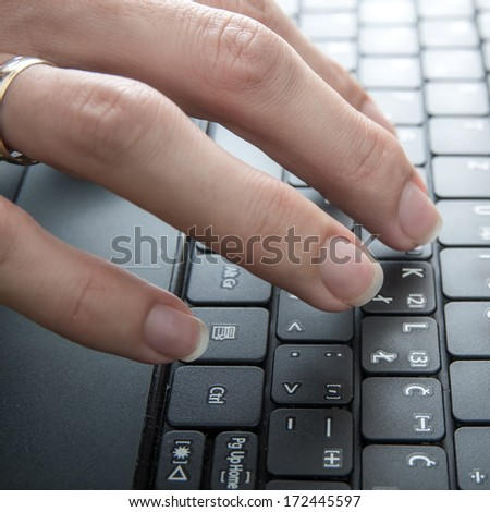 Woman fingers on laptop keyboard in close up - stock photo