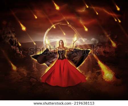 woman fire mage in medieval dress with developing mantle conjured fiery meteor rain - stock photo