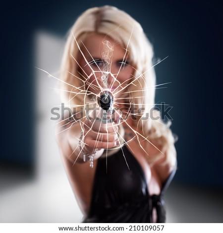 woman firing a gun through a window - stock photo